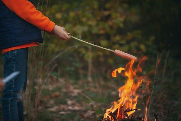 Kid boy braten hotdogs auf stöcken über flammen in einem lagerfeuer.