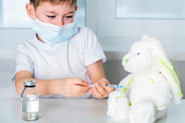 Kid boy in medizinischer schutzmaske spielt, stofftier beimpfen.