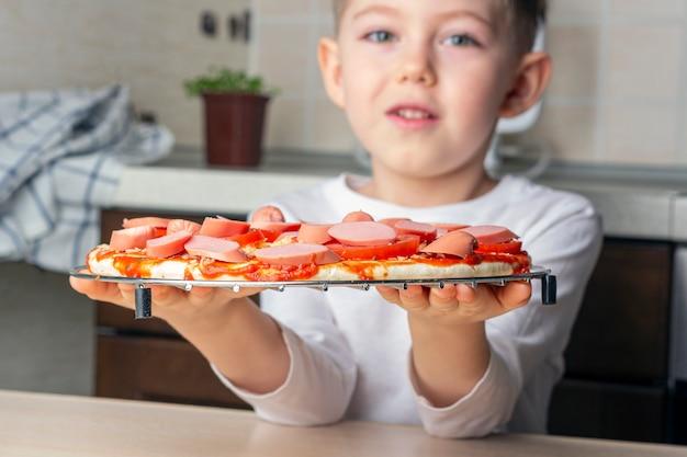 Kid boy kocht hausgemachte pizza. kind hält fertige pizza, um zum ofen geschickt zu werden. vorschulkinderfähigkeiten, kleiner helfer. familienfreizeit.