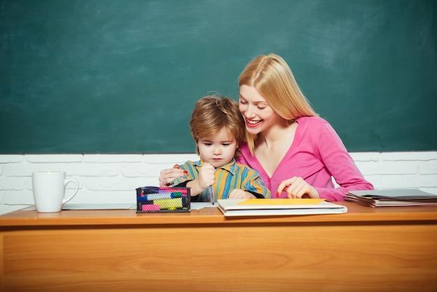 Kid kleiner junge und lehrerin lehrerin klassenzimmer. entwicklung und erziehung. schulkindergarten und entwicklung. talente und fähigkeiten entwickeln. kinderbetreuung und entwicklung. vorbereitung auf die vorschule.