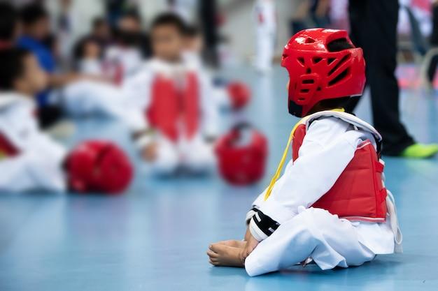 Kid sport athlet taekwondo mit schutzausrüstung vor dem kampf aufwärmen