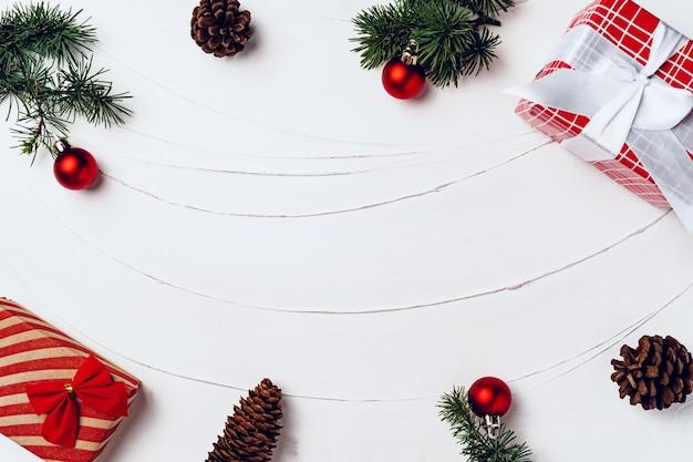 Kiefer verziert mit kugeln und verpackten weihnachtsgeschenken auf weißer hölzerner hintergrundoberansicht