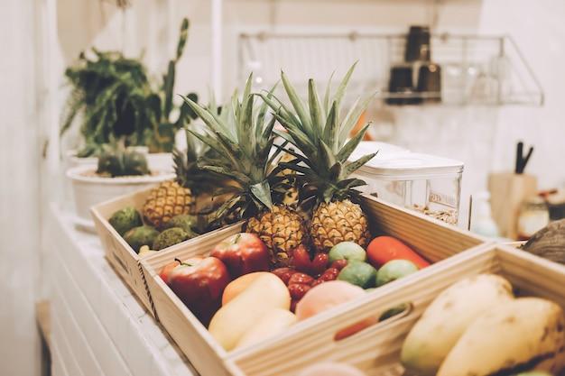 Kiefernapfel, mango, apfel und verschiedene obstsorten in holzkiste.
