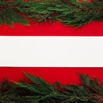 Kiefernblätter auf einem roten hintergrund mit einer leeren anmerkung