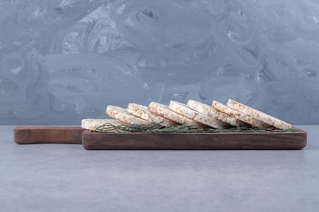 Kiefernblätter schmücken ein tablett mit keksen auf marmor