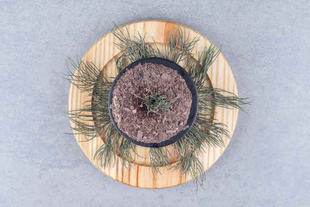 Kiefernblätter und ein kuchen auf einer holzplatte auf marmortisch.