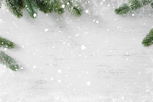 Kiefernblätter verziert als rahmen auf einem weißen hölzernen hintergrund mit schneeflocken. frohe weihnachten und winterurlaub hintergrund.