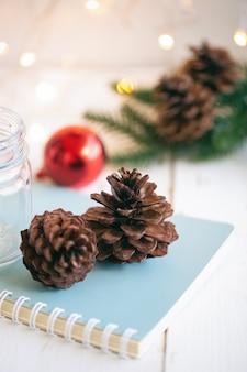 Kiefernkegel oder nadelbaumkegel auf blauem notizbuch nahe flasche und rotem blasenball auf weißer hölzerner planke mit goldenem hellem bokeh hintergrund. süßer vertikaler hintergrund für weihnachts- und wintersaisontapete.
