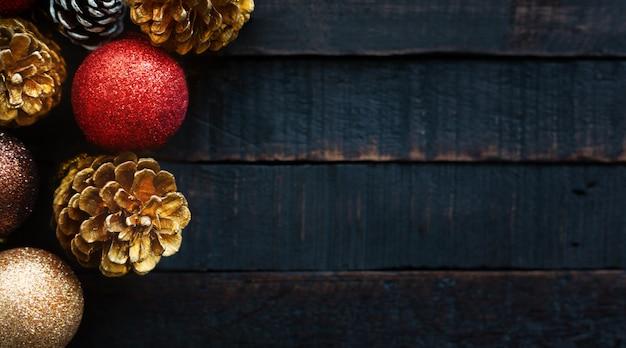 Kiefernkegel- und weihnachtsdekorationsbälle auf dunklem hölzernem hintergrund.