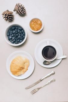 Kiefernzapfen; blaubeeren; marmelade; brot und kaffeetasse auf weißem hintergrund