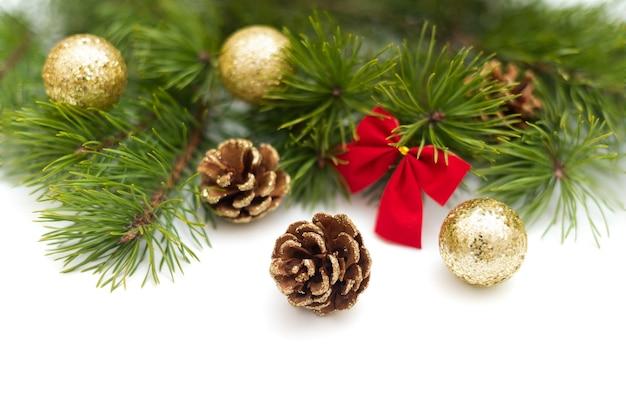 Kiefernzweig, verziert mit goldenen glitzertannenzapfen, glänzenden goldenen kugeln und einer kleinen roten schleife auf weißem grund. weihnachtskomposition, kopierraum, vorlage für eine grußkarte oder einladung.