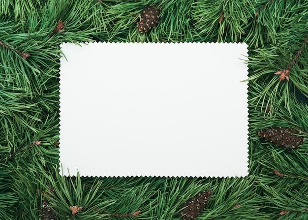 Kiefernzweigrahmen mit weißem anmerkungspapierblatt für text. weihnachten und neujahr hintergrund