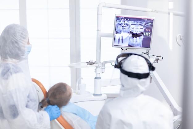 Kieferorthopäde, die digitale radiographie während des besuchs von kinderpatienten analysiert, die in ppe gekleidet sind. stomatolog im schutzanzug für coroanvirus als sicherheitsvorkehrung beim betrachten der digitalen röntgenaufnahme der kinderzähne während der konsultation