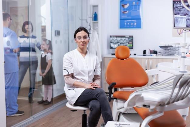 Kieferorthopäde in der zahnarztpraxis, die neben dem werkzeugfach sitzt, mit assistentin, die mit patienten im hintergrund diskutiert. stomatolog in professioanl zahnklinik lächelnd in uniform mit blick auf die kamera.