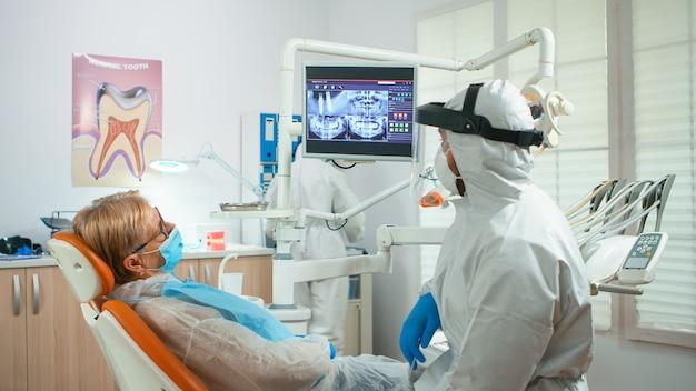 Kieferorthopäde in spezieller ausrüstung, die auf digitales röntgen zeigt, um die zahnbehandlung während der globalen pandemie zu erklären. ärzteteam im gespräch mit einer frau mit gesichtsschutz, schutzanzug, maske und handschuhen