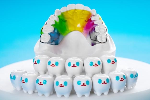 Kieferorthopädisches gerät mit zahnhalter und zahnärztliche instrumente auf blauem grund.