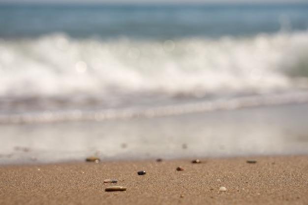 Kiesel am tropischen strand mit verschwommenen wellen im hintergrund.
