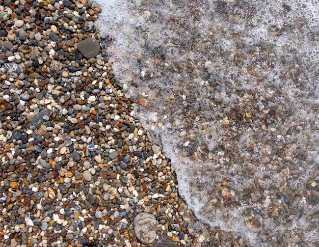 Kieselsteine am meeresstrand. die wogenden wellen des meeres mit schaum