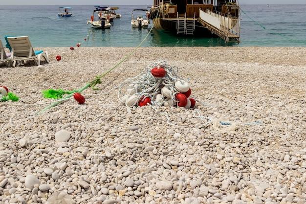 Kieselsteine am meeresufer mit dem am ufer festgemachten schiff