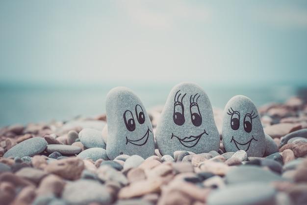 Kieselsteine mit gezeichneten gesichtern im sand. vater, mutter und tochter. familienberufungskonzept.