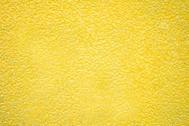 Kiesstein gemalter gelber beschaffenheitshintergrund.
