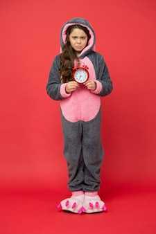 Kigurumi-pyjamas für ihren komfort. lustiges kind im häschenpyjama. unterschiedliche tageszeiten und kinderplankonzept. wecker morgens. trauriges kind, das zum schlafen pyjama trägt. check-up-zeit.