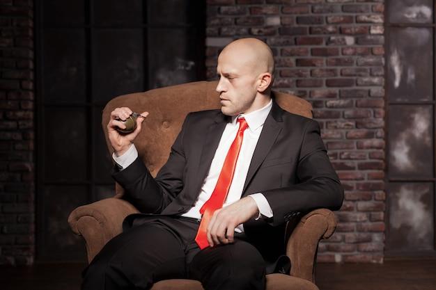 Killer in anzug und krawatte bereit, eine granatennadel zu ziehen