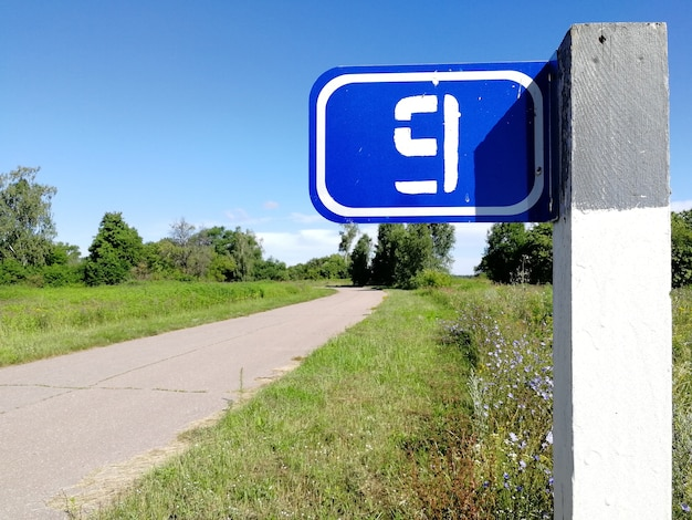 Kilometerzeichen mit der nummer 9 auf dem pfosten einer landstraße im sommer.