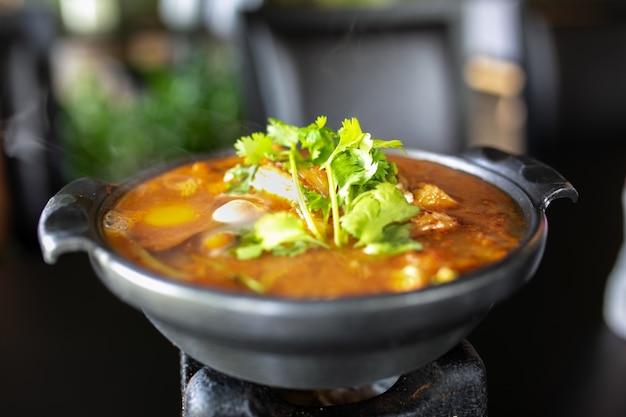 Kimchi-suppe mit rohen hühnereien und weißem tofu, populäres koreanisches lebensmittel.