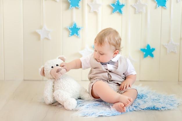 Kind 1 jähriger junge, der mit einem teddybär in einem anzug und einer fliege sitzt