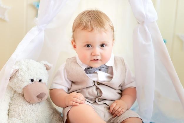 Kind 1 jahr ein junge im anzug sitzt mit einem bären in einem wigwam in einem fotostudio, geburtstag eines kindes 1 jahr