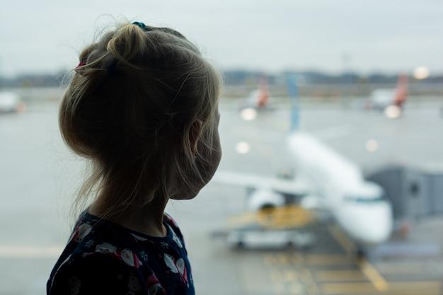 Kind am flughafen schaut auf das flugzeug vor dem fenster