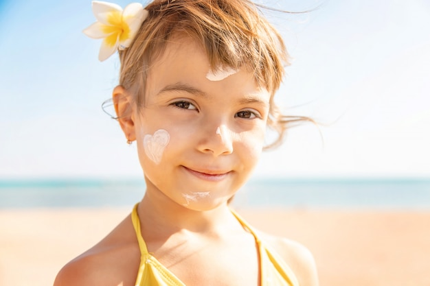 Kind am strand schmiert sonnencreme. selektiver fokus