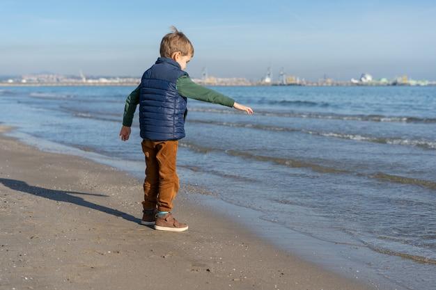 Kind am ufer des strandes spielt mit den wellen