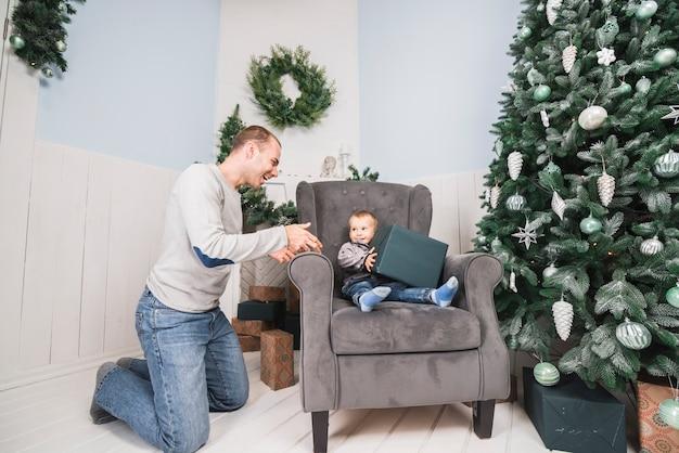 Kind auf couch mit großem geschenk