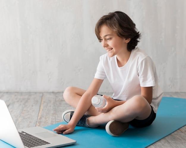 Kind auf dem boden neben dem laptop