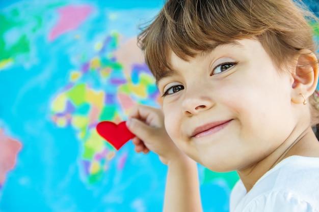 Kind auf dem hintergrund der weltkarte. mag es zu reisen. selektiver fokus