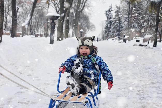 Kind auf dem schlitten im winterpark