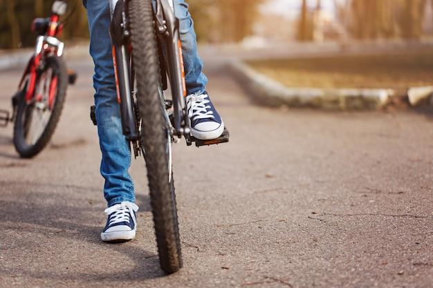 Kind auf einem fahrrad an der asphaltstraße am sonnigen frühlingstag. nahaufnahme auf pedal und fuß