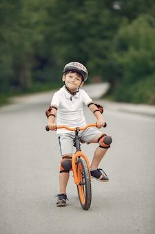 Kind auf einem fahrrad an der asphaltstraße im sommer. fahrrad im park
