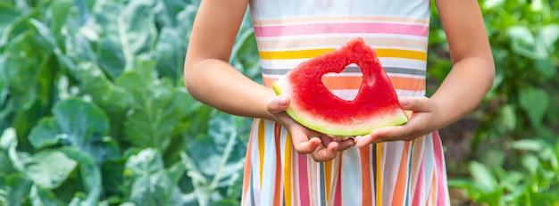 Kind auf einem picknick isst eine wassermelone.