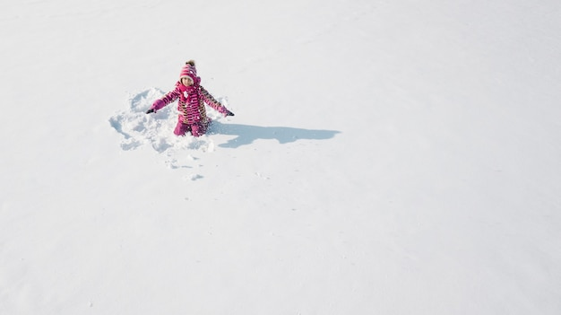 Kind auf einem schnee, der einen schneeengel macht. luftaufnahme von oben. sie trägt rote kleidung