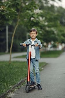 Kind auf tretroller im park. kinder lernen rollschuh laufen. kleiner junge, der am sonnigen sommertag schlittschuh läuft.