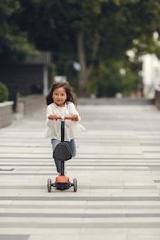 Kind auf tretroller im park. kinder lernen rollschuh laufen. kleines mädchen, das am sonnigen sommertag schlittschuh läuft.