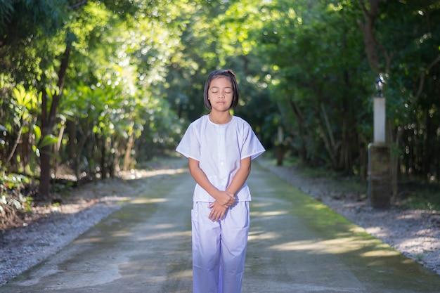 Kind auf weiße kleidung, praxis waling meditation im wald baum mit frieden im auge