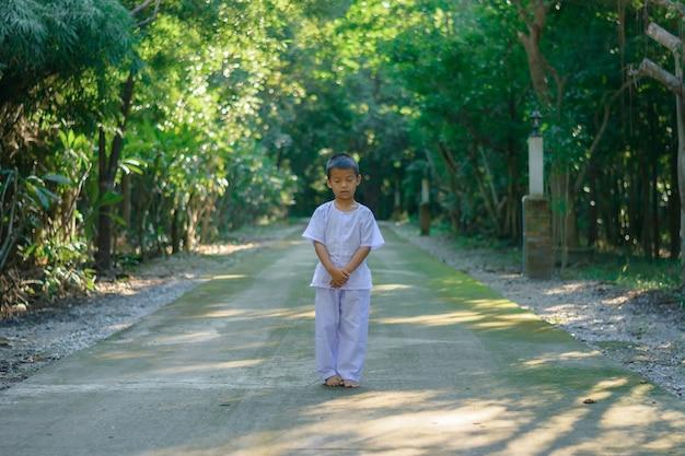 Kind auf weiße kleidung, übung zu fuß meditation im wald baum mit frieden in min