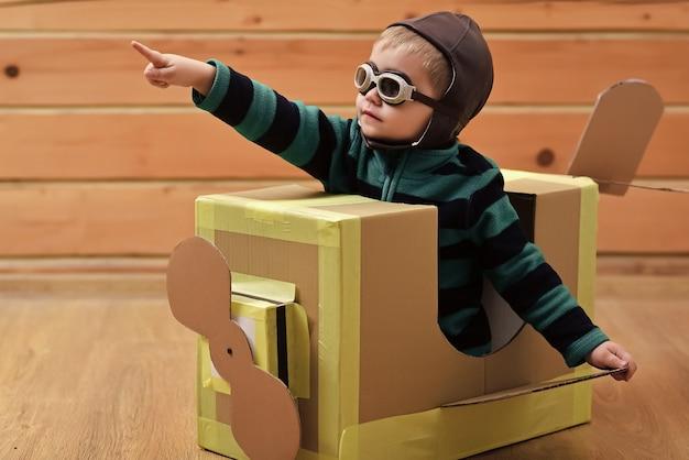 Kind baby ist pilot. kinderreisen, fantasie. kleines jungenkindspiel im pappflugzeug, kindheit. luftpostzustellung, flugzeugbau. traumabenteuer.