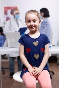 Kind bei ärztlicher untersuchung im krankenhausbüro während der globalen pandemie