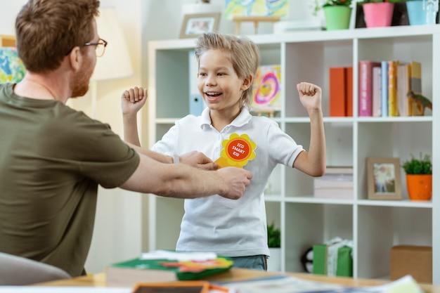 Kind bekommt zeichen. lächelndes ausdrucksstarkes junges kind, das aufgeregt die hände hebt, während der lehrer ein schild auf der brust anwendet