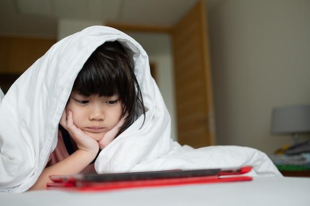Kind beobachtet tablette auf dem bett in der nacht